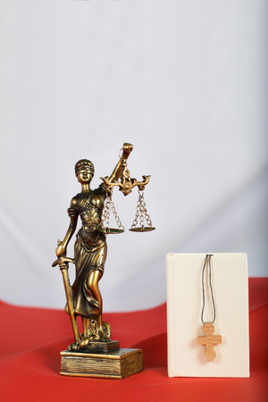Bible and statue of Themis. Polish flag as a background. Closeup