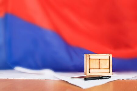 Wooden calendar with free text in front of Russian flag. Russian pass, pen and ballot paper in the background.