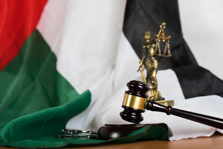 Judge's gavel on a flag of the United Arab Emirates. Statue of Themis and handcuffs in the background