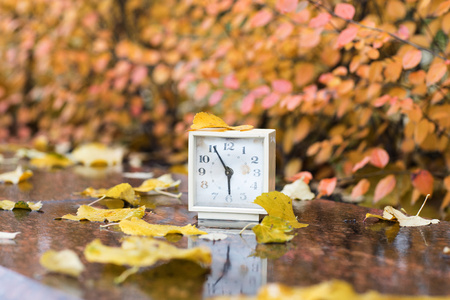 Old square alarm clock on a marble stone covered by rain. Closeup