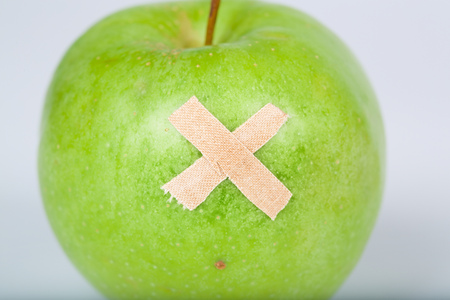 Adhesive bandage on a green apple. Closeup