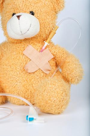 Plush teddy bear with blood transfusion system. Closeup