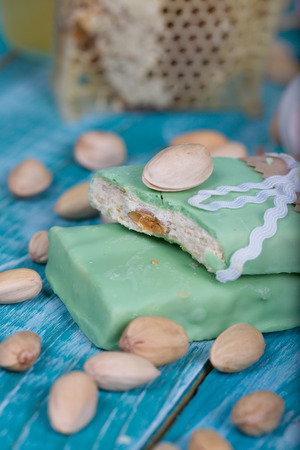 Almond turron covered by pistachio chocolate on a wooden surface. Closeup Zdjęcie Seryjne