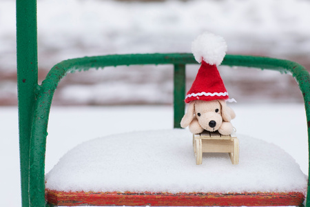 Winter holidays background:  small plush dog in Santa hat on a snowy swing. Closeup