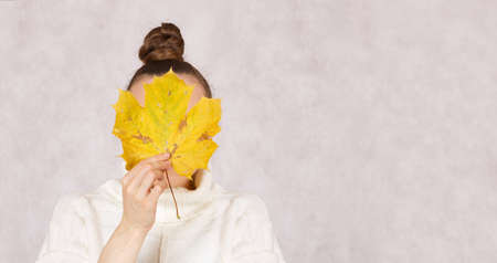 Young caucasian lady between 30 and 40 years dressed in a knitted sweater with yellow maple leaf. Closeup