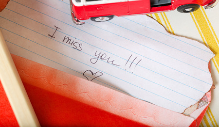 Message on a piece of paper- I miss you. Mini bus in an open drawer. Closeup
