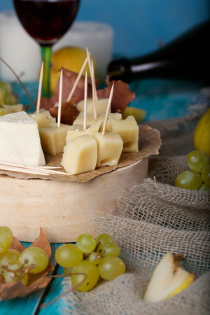 Cheese slices, pear, and grapes on a wooden stand. Closeup