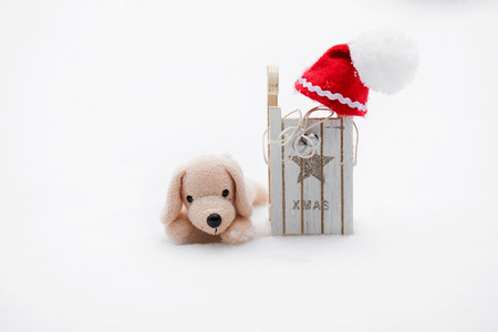 Winter holidays background:  small plush dog in Santa hat on a snow. Closeup