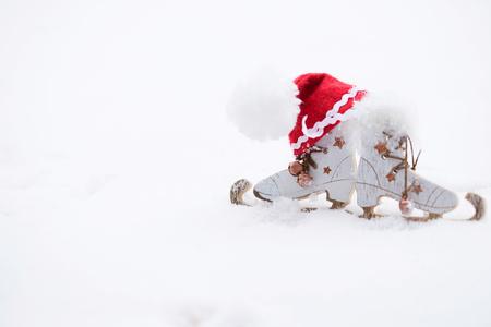 Winter holidays background:  wooden made skates and Santa Claus hat. Closeup