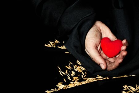 Palm of a peasant woman with plush red heart on a black fabric. Closeup