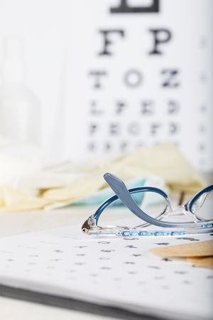 Eyeglasses for children on a eye chart close to eye pads. Closeup