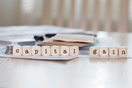 Word  CAPITAL GAIN composed of wooden letters. Closeup