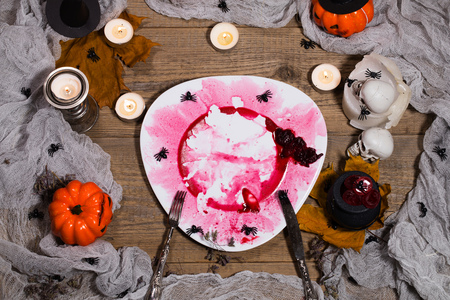 Dirty red plate with silver cutlery on Halloween table. Closeup