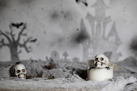 Skull on an old used thick candle. Scary Halloween background. Closeup Фото со стока