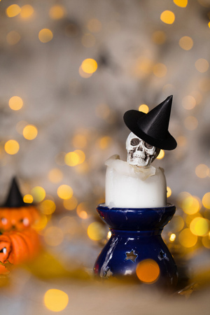 Skull on an used old candle. Spooky halloween background Фото со стока