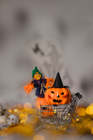 Witch and orange pumpkin in black hat in the small shopping cart. Spooky background. Closeup