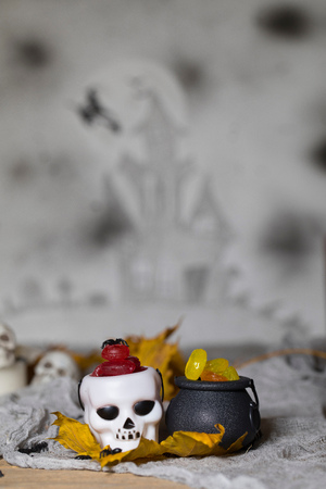 Trick or treat! Candles in cauldrons for Halloween. Handmade witch in the background