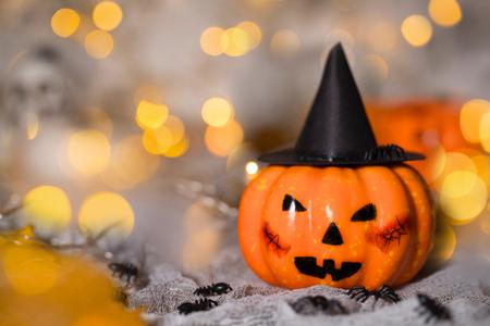 Orange pumpkin in a black witch hat. Spooky background. Closeup
