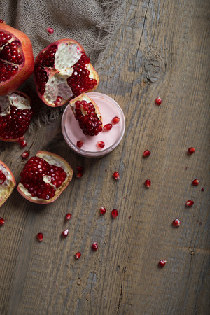 Pomegranate body cream on a wooden surface. Closeup