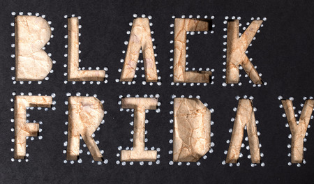 Words BLACK FRIDAY are cut out from black carton paper. Closeup.