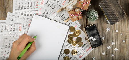 Blank sheet of paper and small purse with coins on the New Year's background. Top view Banco de Imagens