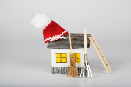 Small handmade paper house and Santa Claus hat on it. Gardening tools in the background
