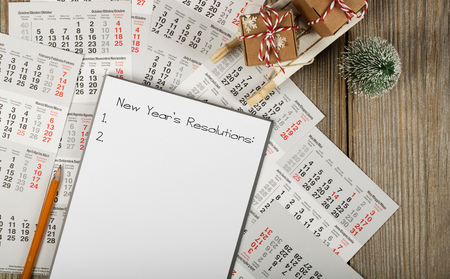 Sheet of paper with new years resolutions on a new years background. Top view