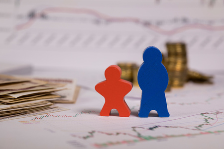 Wooden figurines in red and blue on a diagram. Coins in the background. Stok Fotoğraf - 117189394