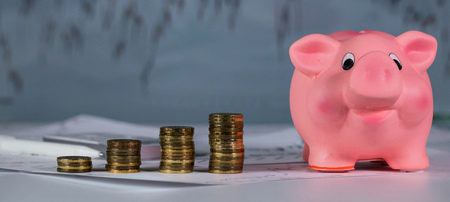 Four stacks of 10 roubles and pink piggy bank. Closeup. Stock market diagram in the background. 스톡 콘텐츠