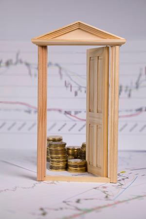 Coins on a stock market charts behind opened small wooden door. Closeup