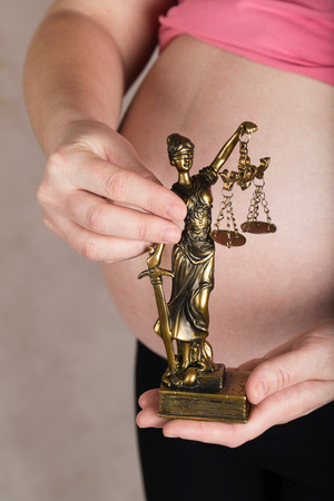 Young pregnant between 30 and 35 years old woman keeps statue of Themis. Closeup