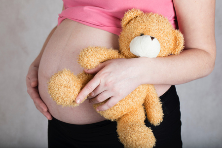 Young pregnant between 30 and 35 years old woman keeps plush brown teddy bear. Closeup Stock Photo