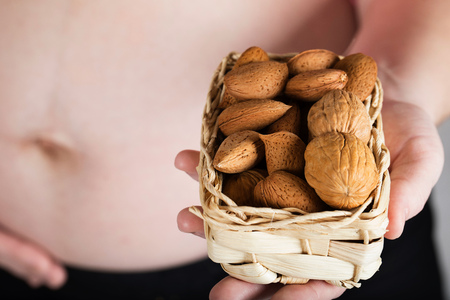 Young pregnant woman keeps woven mini basket full of nuts. Closeup Stock Photo