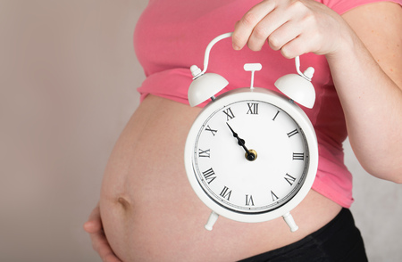 Young pregnant between 30 and 35 years old woman keeps vintage alarm clock close to her belly. Closeup