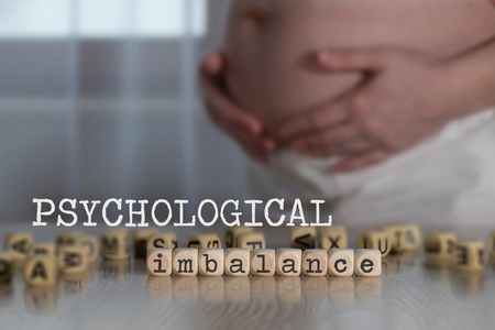 Words PSYCHOLOGICAL IMBALANCE composed of wooden letters. Pregnant woman in the background Foto de archivo