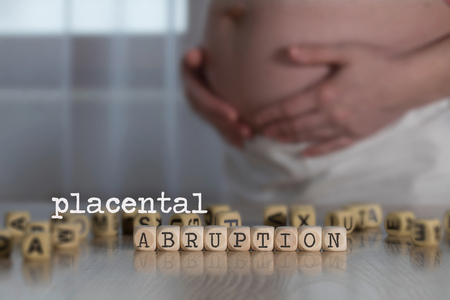 Words PLACENTAL ABRUPTION composed of wooden letters. Pregnant woman in the background