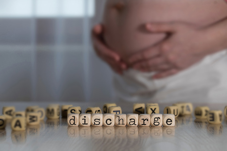 Word DISCHARGE composed of wooden letters. Pregnant woman in the background