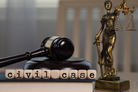 Words CIVIL CASE composed of wooden dices. Wooden gavel and statue of Themis in the background. Closeup Stock Photo