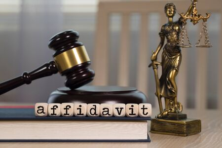 Word AFFIDAVIT  composed of wooden dices. Wooden gavel and statue of Themis in the background. Closeup Archivio Fotografico
