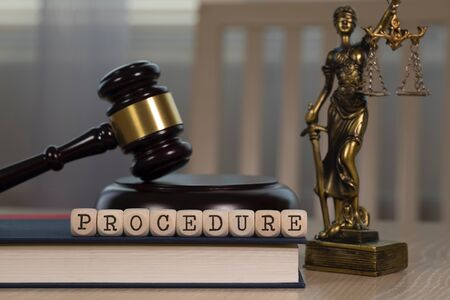 Word PROCEDURE  composed of wooden dices. Wooden gavel and statue of Themis in the background. Closeup