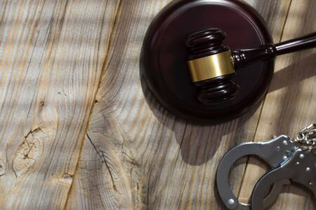 Wooden gavel and handcuff on a wooden surface. Closeup