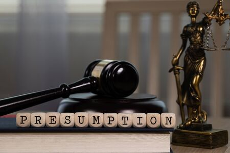 Word PRESUMPTION  composed of wooden dices. Wooden gavel and statue of Themis in the background. Closeup