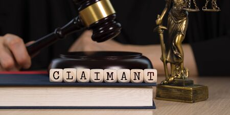 Word  CLAIMANT composed of wooden dices.  Wooden gavel and statue of Themis in the background. Closeup