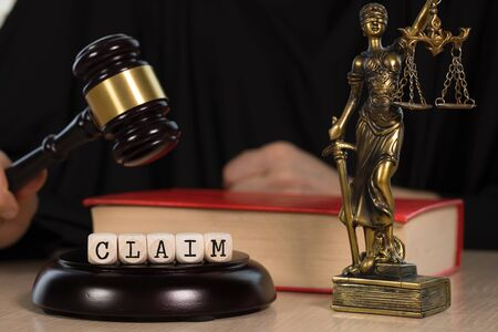 Word CLAIM composed of wooden dices.  Wooden gavel and statue of Themis in the background. Closeup