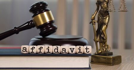 Word AFFIDAVIT  composed of wooden dices. Wooden gavel and statue of Themis in the background. Closeup Stock Photo