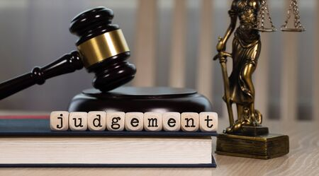 Word  JUDGEMENT composed of wooden dices. Wooden gavel and statue of Themis in the background. Closeup