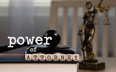 Words POWER OF ATTORNEY  composed of wooden dices. Wooden gavel and statue of Themis in the background. Closeup Stock Photo