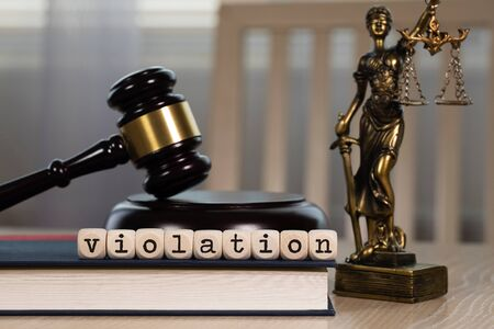 Word VIOLATION composed of wooden dices.  Wooden gavel and statue of Themis in the background. Closeup
