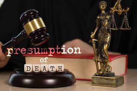Words PRESUMPTION of DEATH  composed of wooden dices. Wooden gavel and statue of Themis in the background. Closeup