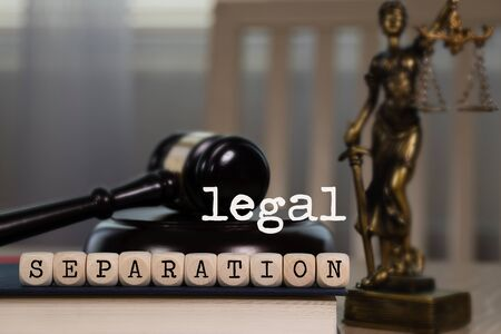 Words LEGAL SEPARATION composed of wooden dices. Wooden gavel and statue of Themis in the background. Closeup